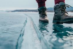 the girl went for a walk before dawn. walking on a frozen pond. winter vacation. the girl goes on the ice. boots do not slip