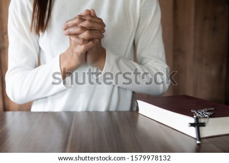 The girl wishes to God. In the hand there was a cross and placed on the Bible. Concept of prayer, prayer for salvation from suffering, Christ's religion. believe. Prayer for prayer. #1579978132