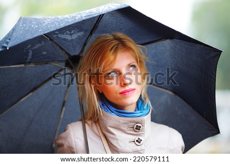 the girl with a black umbrella costs in the rain