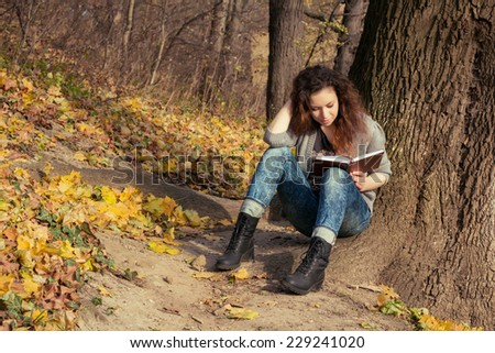 The girl with a book under a tree. Lonely beautiful girl with a book in autumn park.