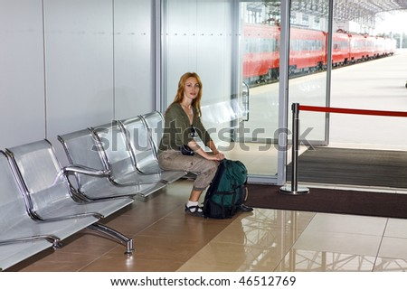 The girl with a road backpack in a station waiting room