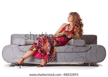 The girl with a wine glass on a sofa