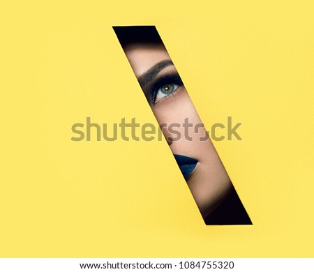 The girl with beautiful green bright eyes with brown shadows, lipstick of the color of the sea wave and expressive eyebrows looks into the hole of the colored paper. #1084755320