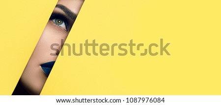 The girl with beautiful green bright eyes with brown shadows, lipstick of the color of the sea wave and expressive eyebrows looks into the hole of the colored paper.