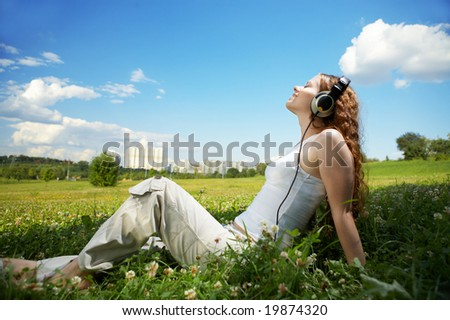 The girl with headphones against park and the sky