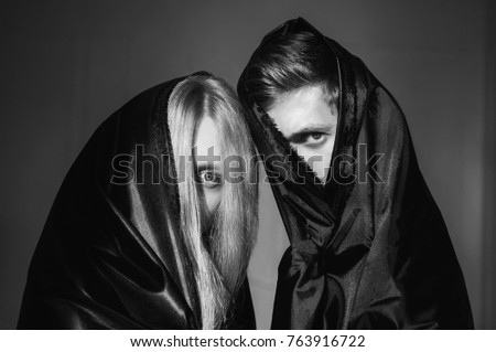 Stock Photo The girl with long blonde hair and a man in black cloth on faces. Conceptual photography. Piercing look. Anonymity. Portrait photography.