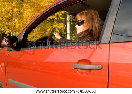 The girl with sunglass sits in the red car