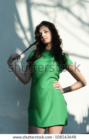 the girl with the green dress smiles with sensuality