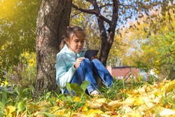 the girl with the tablet sits under a tree in the autumn park