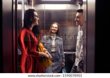 The girls and the guy ride in the elevator. Students go to study. People in the elevator. Elevator with people, communication in public places. Colleagues go to work in the elevator.