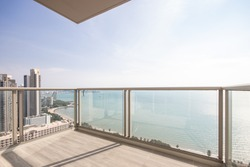 The glass balcony overlooks the sea.