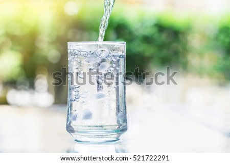 the glass of Cool fresh drink with ice cube and bubble on the  table