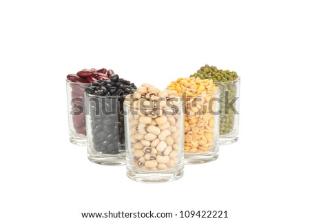 The glass of different legumes are  on a white background