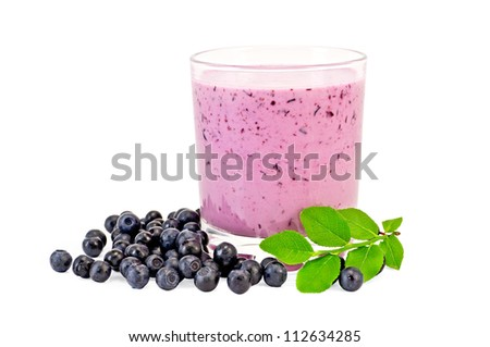 The glass of milkshake, berries and green sprig of blueberries isolated on white background