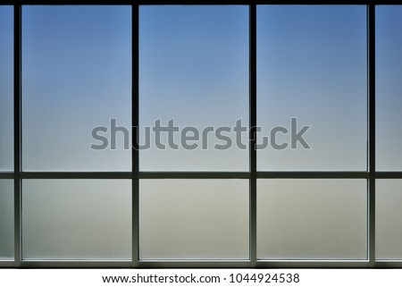 The glass window of building with white aluminum framework, Blue tone as background.