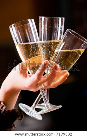 The glasses of champagne in the hand on the black background