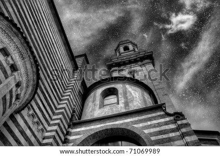 The glory of God\'s Universe. The night sky above an Italian church. Black and white.