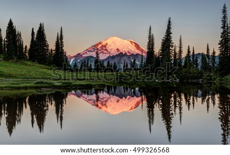 The Glowing Peak of Mount Rainier at Dawn with a calm reflection from the shore of Tipsoo Lake. Mount Rainier National Park, Washington State, USA