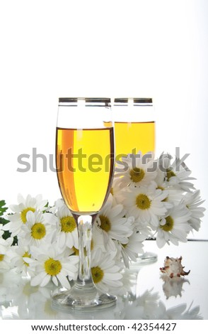 The Goblets with wine and seashells. White daisywheels are reflected on surfaces