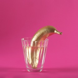 the golden banana is in a glass cup