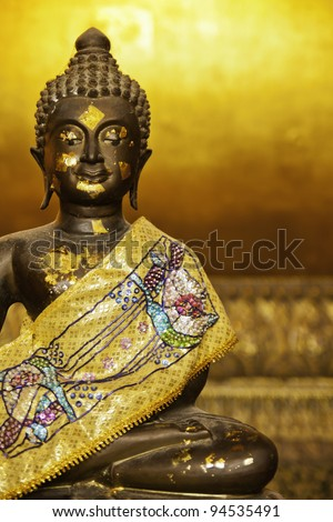 The golden black buddha statue in the setting posture.