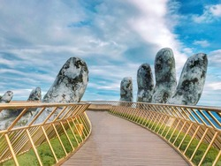 The Golden Bridge is lifted by two giant hands in the tourist resort on Ba Na Hill in Danang, Vietnam. Ba Na Hill is a favorite destination for tourists.