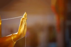 The golden Buddha's hand extended from his body and his thumb and forefinger touched.