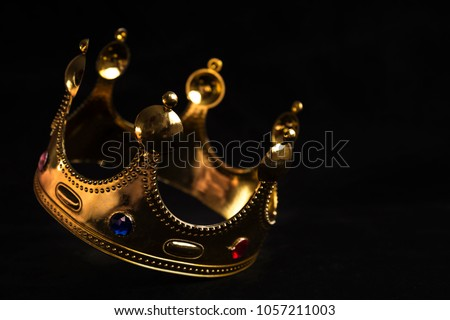 the golden crown of the king on a black background in the fall