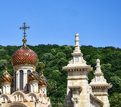 The golden domes of the Christian church glisten in the sun against the blue sky. Several yellow onion domes of the church. Orthodox church with domes and crosses. Christian Faith Concept
