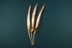 The Golden feather. Pattern with gold colored feathers on a trendy green emerald background. The view from the top. Flatly.