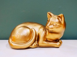The golden figurine of the cat lies on the shelf against the background of the gray blue wall