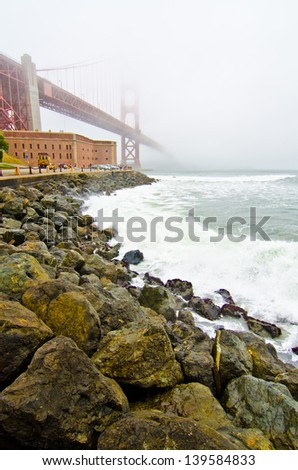 The Golden Gate Bridge runs over Fort Point and disappears into the fog on a typical San Francisco day.