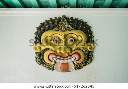 the  golden giant mask on the white wall inside of the very old castle in Indonesia #517262545