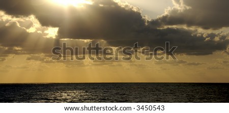 The golden rays of a sunset at sea bursts through the clouds