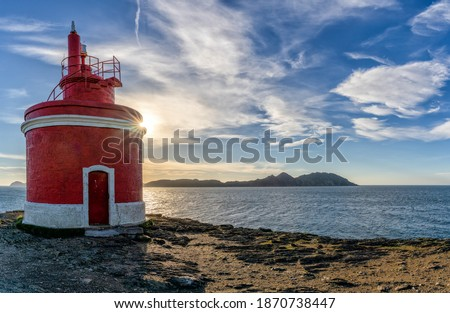 The golden sun behind the Punta Robaleira lighthouse in Galicia and the Cies Islands behind Stok fotoğraf ©