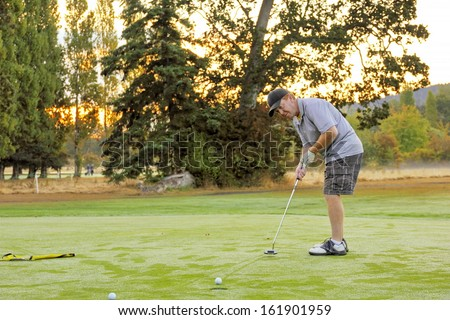 The golf ball runs slowly across the green to the cup leaving trails in the heavy dew on the autumn morning golf green as the sun rises behind the golfer\'s shoulder promising dryer greens soon.
