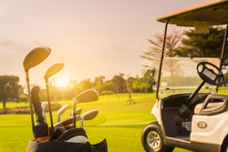 The Golf club bag and golf carts for golfer training and play in game with golf course background , green tree sun rays