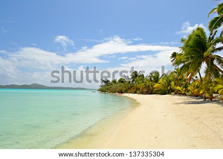 The gorgeous turquoise sea and desert beach in Ee Island. Woman walking on the beach. Location: Aitutaki atoll, Cook Islands.