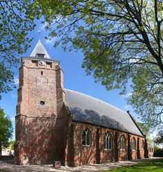 The gothic church of Serooskerke village with its massive brick tower between some churchyard trees in the Netherlands
