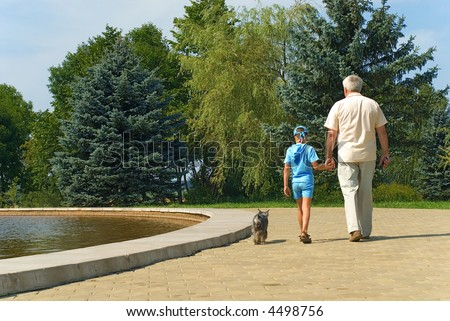The grandfather, grandson and dog walk in park