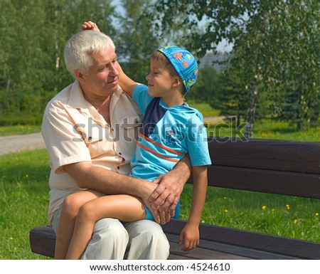 The grandfather holds grandson in a lap park - stock photo