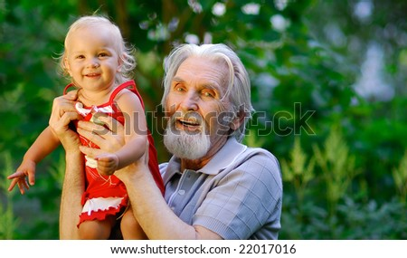 The grandfather sits on a lawn and holds the cheerful grand daughter on hands. They are shined by the coming sun.