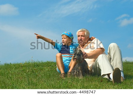 The grandfather with grandson and a dog look in distance