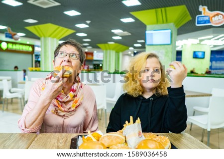 The grandmother raises the baby to eat fruit, and she eats a hamburger with pleasure. healthy eating and fast food