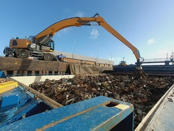 The grapple loading and unloading crane unloads metal and metal waste for recycling from the ship's hold. Ferrous scrap, non-ferrous scrap. Import and export of scrap for processing