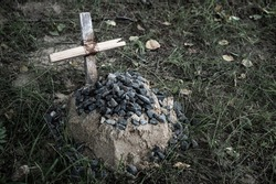 the grave of the family's beloved pet, a sand mound and a hand-made wooden cross