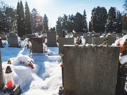 The gravestones In A Cemetery Covered In Snow. Silent place.  Shining candle laterns.