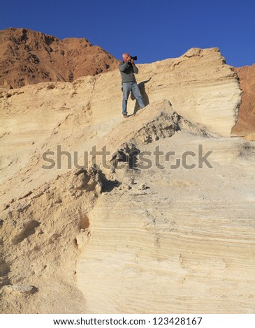The gray-haired man photographs in a canyon at coast of the Dead Sea. On a shoulder at it a bag of the professional photographer.