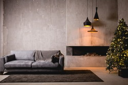 The gray velor sofa in the dark loft room has a bright light from the eternal light and an artificial fireplace. Inner attic with concrete walls and a decorated Christmas tree with gift boxes