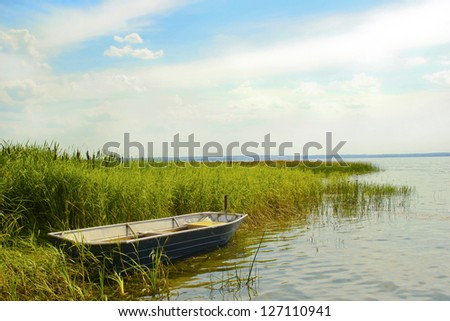 The great boat floats on the shore of Plesheevo lake in the summer in Russia.